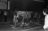 Overturned burnt out car Notting Hill Carnival riots London 1976 - Martin Mayer - ,1970s,1976,AUTO,AUTOMOBILE,AUTOMOBILES,AUTOMOTIVE,BAME,BAMEs,Black,BME,bmes,burn,burning,BURNS,burnt,Burnt Out,car,Carnival,Carnivals,cars,cities,City,CLJ,Conflict,Conflicts,diversity,ethnic,ethnicit