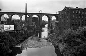Stockport, Northern industrial landscape, river Mersey, mill and railway viaduct, once the biggest in the world, carrying the West Coast Main line, with a billboard advertising Give him Guinness and t... - Martin Mayer - 1970,1970s,advertising,billboard,BILLBOARDS,bridge,bridges,building,buildings,carries,carry,carrying,catering,cities,City,cityscape,cityscapes,Coast,coastal,coasts,EBF,Economic,Economy,Greater,Guinnes
