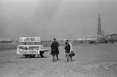 Family wonders whether to try some seafood from a cockle and mussel stall, Blackpool beach, Lancashire 1970 - Martin Mayer - 1970,1970s,and,beach,BEACHES,Blackpool,buy,buyer,buyers,buying,COAST,coastal,coasts,cockle,cockles,commodities,commodity,families,family,goods,holiday,holiday maker,holiday makers,holidaymaker,holiday