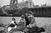 Young family from mill town Ashton-under-Lyne on the beach at Blackpool during Wakes Week - Martin Mayer - 1970,1970s,adult,adults,Ashton-under,beach,BEACHES,Blackpool,boy,boys,child,CHILDHOOD,children,COAST,coastal,coasts,DAD,DADDIES,DADDY,DADS,families,Family,father,FATHERHOOD,fathers,female,females,girl
