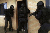 Armed Police with gas masks forcing their way in, firearms and tactical training at the Cleveland and Durham Police Tactical Training Centre, Stockton. - Mark Pinder - 08-08-2001