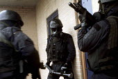 Armed Police with gas masks forcing their way in, breaking down the door with a ram, firearms and tactical training at the Cleveland and Durham Police Tactical Training Centre, Stockton. - Mark Pinder - 08-08-2001