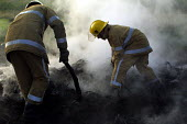Firefighters put out a fire of abandoned tyres on empty land near North Shields. 23/9 2001. - Mark Pinder - 23-09-2001
