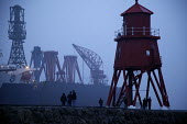 End of an era on the Tyne. Tynesiders gather at the Groyne in South Shields to say their final farewells to the Swan Hunter shipyard cranes as they leave the river Tyne, on a journey to the Bharati s... - Mark Pinder - ,2000s,2009,barge barges,boat,boats,capitalism,capitalist,closed closure,crane cranes,deindustrialisation,Deindustrialization,DOWNTURN,EBF Economy,engineering industry,export,export exports,exporting,