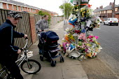 A young woman with a pushchair stops to read floral tributes and cards left around a tree in memory of a young motorcyclist killed when his bike hit a tree. Silkeys Lane, North Shields, Tyne and Wear,... - Mark Pinder - 12-05-2004
