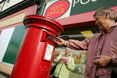 A woman posts a letter into a traditional red postbox outside a Post Office, North Shields. - Mark Pinder - 2000s,2004,box boxes,EBF economy business & finance,Letter box,Letter boxes,letter letters,Letterbox,Letterboxes,MAIL,outside,pillar box,POST,post box,postal,postbox,posting,public,public services,roy