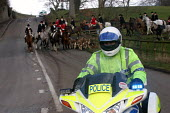 A motorcycle policeman escorts members of the Percy Hunt back to their stables the day after the hunting ban came into force in England and Wales. Alnwick, Northumberland, 19/2 2005. - Mark Pinder - 2000s,2005,adult,adults,animal,animal animals,animals,bike,bikes,blood sports,canine,canter,clj ,country,countryside,dog,dogs,domesticated ungulate,domesticated ungulates,equestrian,equine,escort,forc