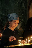 A young girl light a candle at Friday Mass at the Georgian Orthodox Sameba Church, Tbilisi, Georgia, 20/5 2005. - Mark Pinder - 20-05-2005