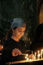 A young girl light a candle at Friday Mass at the Georgian Orthodox Sameba Church, Tbilisi, Georgia, 20/5 2005. - Mark Pinder - ,2000s,2005,Apostolic ,candle candles,candle candles light,Catholicism,Caucasus,christian christians,christianity Christian,Church,churches,congregation,Georgia,Georgian,girl girls,god,Mass,monotheist