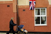 A woman pushes a pram past a Union Jack draped from a house in Easington Colliery, Co Durham on the day of the Queens visit to the former mining town.The graffiti on the wall reads fuck - Mark Pinder - 08-05-2002