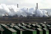Corus Teesside steelworks, Redcar Co' Cleveland with Holiday Chalets are in the forground. - Mark Pinder - 2000s,2003,accommodation,capitalism,capitalist,EBF economy,ENI environmental issues,environmental degradation,FACTORIES,factory,Holiday,Holiday Chalet,HOLIDAYS,housing,Industries,Industry,lfl leisure,