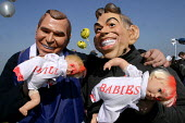 Peace protestors wearing Tony Blair and George W. Bush masks carry a pair of dolls emblazoned with I Kill Babies at the Foil the Base event. Menwith Hill listening base, North Yorkshire. 22/3 2003. - Mark Pinder - 22-03-2003