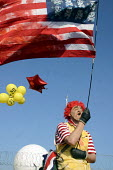 A protestor dressed as Ronald McDonald with a blood stained pastiche of the American stars and stripes and stull and crossbones of death at the Foil the Base event. Menwith Hill listening base, North... - Mark Pinder - 22-03-2003