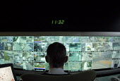 CCTV control centre with a worker watching the public on multiple screens, Tower Hamlets, London - Marco Secchi - 10-08-2006