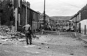 British soldier and burnt out bus, Catholic Ardoyne district, Belfast 1969 shortly after deployment of British troops to Northern Ireland following days of rioting - NLA - 1960s,1969,Ardoyne,armed,Armed Forces,arms,army,Belfast,British,British Army,Burnt Out,bus,bus service,buses,Catholic,catholics,cities,city,communities,community,conflict,conflicts,FAL Rifle,FN,gun,gu