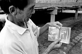 China: A father shows a picture of his daughter who was trafficked into the sex industry. - Nick Rain - 20-08-2003
