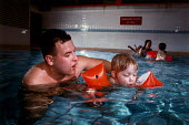A swimming instructor at a local leisure centre teaches a little girl to swim with the help of water wings. He is a local government employee. - Paul Carter - 1980s,1989,child,CHILDHOOD,CHILDREN,class,communicating,communication,Council Services,Council Services,EDU education,EXERCISE,exercises,government,job,jobs,juvenile,juveniles,kid,kids,LAB LBR work,le