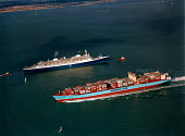 Aerial view of NCL passenger ship Norway towed by tugs passing the Maersk Line container vessel Regina Maersk. - Paul Carter - 04-10-1996
