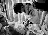 Male charge nurse checks stitches on abdomen of patient after an operation. - Paul Carter - 1980s,1982,HEA health,hospital,HOSPITALS,job,jobs,LAB LBR work,medic,medical,medicine,medics,nurse,nurses,nursing,people,PUBLIC SERVICES,service,SERVICES,stomach,worker,workers,working