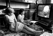 Two girls sitting on the floor watching a cartoon on television. - Paul Carter - 1980s,1983,ACE entertainment,cartoon,CARTOONS,child,CHILDHOOD,children,families,family,female,females,floor,girl,girls,home,juvenile,juveniles,kid,kids,LFL lifestyle & leisure,people,person,persons,ro