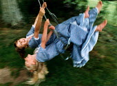 Two teenage girls swinging in a garden. - Paul Carter - 1980s,1989,adolescence,adolescent,adolescents,EMOTION,EMOTIONAL,EMOTIONS,enjoying,enjoyment,families,family,female,females,fun,funny,girl,girls,Humor,HUMOROUS,HUMOUR,joking,LAUGH,laughing,LAUGHTER,LFL