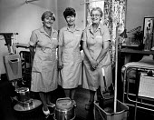 Portrait of three cleaners with cleaning equipment, in hospital ward. - Paul Carter - 1980s,1982,ancillary,and,bucket,care,cleaning,cleansing,equipment,female,group,groups,HEA Health,health,HEALTH SERVICES,healthcare,Hospital,HOSPITALS,job,jobs,LAB LBR work,ladies,mop,National Health S