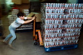Young man pushing a crate of beer cans in a packaging warehouse, it is a sheltered workshop and is run by people with special needs. - Paul Carter - 01-09-1983