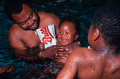 Close up of father and two children, playing in a swimming pool. - Paul Carter - 1980s,1989,arm,babies,baby,BAME,BAMEs,band,bands,black,BME,bmes,child,CHILDHOOD,children,diversity,EARLY YEARS,EMOTION,EMOTIONAL,EMOTIONS,enjoy,ENJOYING,enjoyment,ethnic,ethnicity,EXERCISE,exercises,f