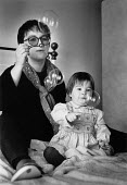 Portrait of a mother and young child sitting on a bed blowing bubbles. - Paul Carter - 20-11-1993