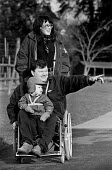 Close-up of a young couple and their son, on a day out. Husband is in his wheelchair, being pushed by his wife. - Paul Carter - 14-12-1993