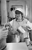 Member of school canteen staff whisking contents of a large saucepan. - Paul Carter - 07-05-1997