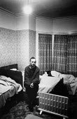 Homeless young man siting on a bed in a temporary night shelter. Brighton - Paul Carter - 23-12-1993