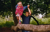 Father helping his daughter to walk across a fallen tree trunk in ancient woodland. - Paul Carter - 1990s,1995,child,CHILDHOOD,CHILDREN,climb,climbing,DAD,DADDIES,DADDY,DADS,daughter,DAUGHTERS,ENI environmental issues,fallen,Father,FATHERHOOD,FATHERS,female,females,forest,girl,GIRLS,helping,juvenile