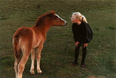 Young girl blows into the nose of a New Forest pony foal. - Paul Carter - ,1990,1990s,animal,ANIMALS,appealing,charming,cute,Domesticated Ungulates,ENI environmental issues,equestrian,equine,female,females,Forest,girl,GIRLS,horse,horses,LEISURE,LFL lifestyle & leisure,peopl