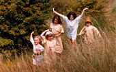Children dressed in medieval costume, running through long grass. - Paul Carter - 1990s,1995,child,CHILDHOOD,Children,costume,dressing up,EMOTION,EMOTIONAL,EMOTIONS,ENI environmental issues,female,females,friend,friends,funny,girl,GIRLS,group,groups,HAPPINESS,happy,historic,history