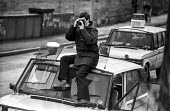Police photographer takes pictures of striking miners at Cortonwood colliery, near Rotherham, Siouth Yorkshire - Peter Arkell - 1980s,1985,adult,adults,AUTO,AUTOMOBILE,AUTOMOBILES,AUTOMOTIVE,camera,cameras,CAR,cars,CLJ,collieries,colliery,Cortonwood,DISPUTE,DISPUTES,evidence,INDUSTRIAL DISPUTE,Land Rover,MATURE,member,member m