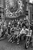 Boys hitch a ride on a union banner at the demonstration of miners and their supporters in Barnsley - Peter Arkell - banner,banner,banners,Barnsley,boys,child,children,community,demonstration,miner,Miner's Strike,the,Miners Strike,Miners,Miners Strike,Miner's Strike,NUM,NUM,protest,demonstration,strike,strike,strike