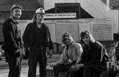 Young Kent miners at Betteshanger colliery in a confident mood during work to rule just before 1974 strike. The graph behind them shows falling production levels due to the work to rule. - Peter Arkell - ,1970s,1974,Betteshanger,capitalism,capitalist,change,Coal Industry,Coal Mine,coalfield,coalindustry,collieries,colliery,coming off,confident,disputes,EBF,Economic,Economy,employee,employees,Employmen