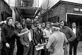 Building workers strike for 35 for a 35 hour week and an end the the Lump 1972. Pickets block a strike-breaker on a site in Camden, London - Peter Arkell - , Scheme,1970s,1972,7,argue,arguing,argument,BAME,BAMEs,black,bme,bme.poc,BME black,bmes,breaker breakers,Building,Building workers strike 1972,BUILDINGS,casual,communicating,communication,conversatio