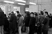 Queueing to sign on at the Brixton Employment Exchange. London - Peter Arkell - 1970s,1971,benefit,benefits,Brixton,cities,city,communicating,communication,dole,employee,employees,Employment,interacting,interaction,job,jobless,jobs,jobseeker,jobseekers,lbr,line,London,male,man,Ma