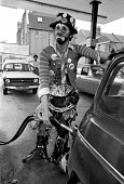 Oil crisis. An unhappy clown filling up the car at a petrol station, London. Petrol prices were rising all the time fueling inflation. 1974 - Peter Arkell - 1970s,1974,3 day week,AUTO,AUTOMOBILE,AUTOMOBILES,AUTOMOTIVE,car,cars,cities,city,clown,clowns,currency,dressed up,driver,drivers,driving,ebf,Economic,Economic Crisis,economy,entertainer,filling,filli