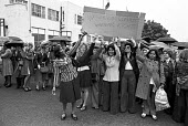 Equal pay strike at Trico, West London. Striking women, members of the AUEW, outside the factory the day after they walked out when management refused to make up the �6 pay differential between men an... - Peter Arkell - ,1970s,1976,AUEW,BAME,BAMEs,black,bme,BME black,bmes,cultural,DISPUTE,DISPUTES,diversity,Equal pay,equal pay strike,equal rights,equality,ethnic,ethnicity,FACTORIES,factory,FEMALE,feminism,feminist,fe