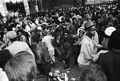 Notting Hill Carnival 1977. Building up towards a riot - Peter Arkell - ,1970s,1977,BAME,BAMEs,Black,BME,bmes,Building,BUILDINGS,Carnival,Carnivals,cities,City,Conflict,Conflicts,crowd,diversity,ethnic,ethnicity,fear,fearful,Hill,male,man,men,minorities,minority,Notting,p
