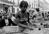 Notting Hill Carnival 1978. Steel band performing on the back of a lorry moving slowly through the streets - Peter Arkell - 1970s,1978,ACE,Arts,BAME,BAMEs,band,bands,Black,BME,bmes,British Steel,BSC,Carnival,Carnivals,cities,City,Culture,diversity,ethnic,ethnicity,FEMALE,HAULAGE,HAULIER,HAULIERS,HGV,hgvs,Hill,instruments,L
