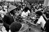 Notting Hill carnival 1977. Steel band makes its way slowly through the streets of Notting Hill - Peter Arkell - 1970s,1977,ACE,Arts,BAME,BAMEs,band,bands,Black,BME,bmes,British Steel,BSC,Carnival,Carnivals,cities,City,Culture,diversity,ethnic,ethnicity,Hill,instruments,male,man,melody,men,minorities,minority,mu