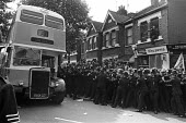 Grunwick strike and lock-out for union recognition of APEX 1977. Strikebreakers bus going past mass picket with the help pf police. - Peter Arkell - Trades Union,1970s,1977,adult,adults,APEX,at,bus,bus buses,bus service,BUSES,CLJ,de recognition,derecognition,dispute,DISPUTES,Grunwick,INDUSTRIAL DISPUTE,industrial relations,mass,mass picket,MATURE,