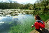 A woman looks across the ponds at Bosherston lily ponds Pembrokeshire Wales - Paul Box - 25-04-2001