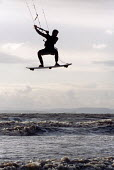 kite surfer jumps high in the air at Weston Super Mare beach - Paul Box - 2000s,2001,activities,activity,adventure,air,beach,BEACHES,big,COAST,coastal,coasts,dangerous,Evening,Exercise,exercises,exercising,extreme,Extreme Sports,flying,force,gale,gales,holiday,holiday maker