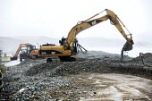 Diggers remove thousands of tons of pebbles off the main road. Storm waves moved a pebble sea defence bank, completely covering the road in Newgale, Pembrokeshire, Wales. - Paul Box - 08-01-2014