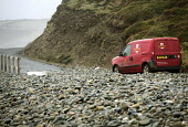 Postman drives across road strewn with pebbles. Storm waves moved a pebble sea defence bank, completely covering the road in Newgale, Pembrokeshire, Wales. - Paul Box - 2010s,2014,bank,BANKS,beach,BEACHES,closed,closing,closure,closures,coast,coastal,Coastal Erosion,coasts,costal defences,damage,damaged,defence,DEFENSE,deliveries,DELIVERING,delivery,employee,employee